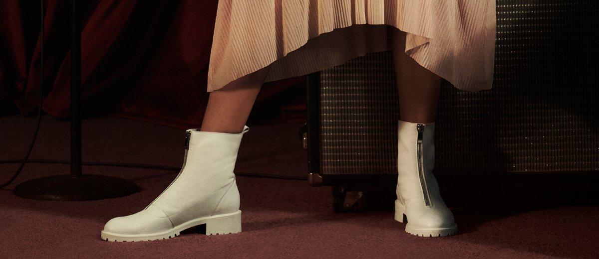 Frauenbeine tragen weiße Chelsea Boots
