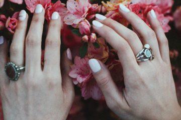 Manikürte Fingernägel vor Rosenstrauch