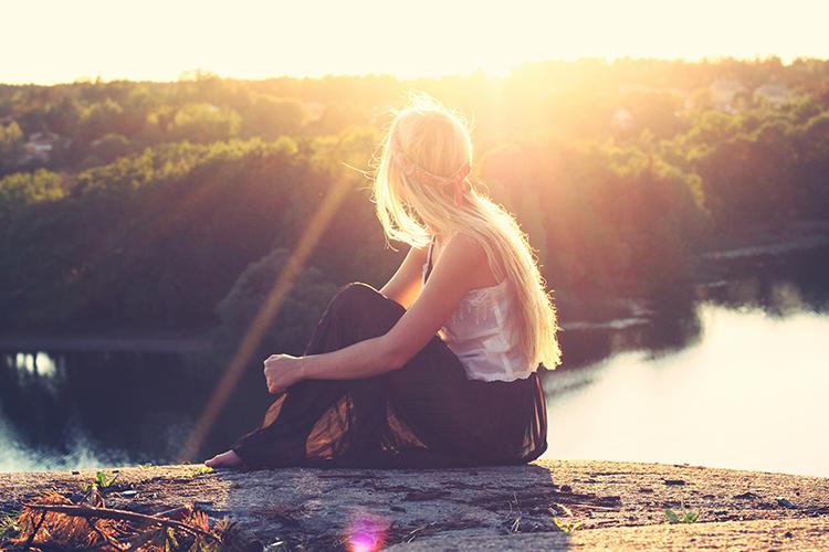 Frau sitzt auf Stein und schaut in die Ferne