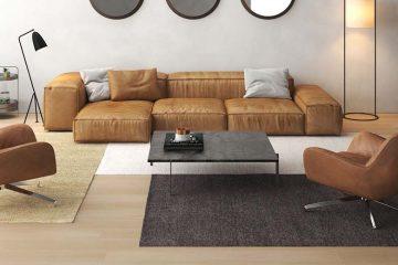 Wohnzimmer mit brauner Couch und rustikalem Teppich