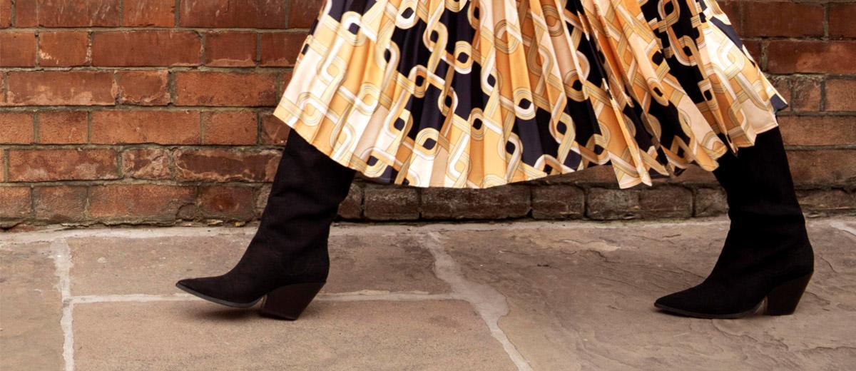 schwarze Cowboy Stiefel von Richard Allan x H&M vor roter Wand aus Backsteinen