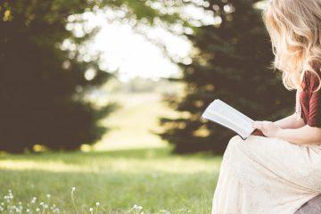 Frauen-Ratgeber wird von blonder Frau in der Natur gelesen