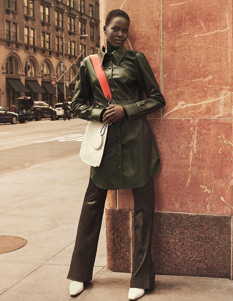 Trend-Mäntel in Leder von HM getragen von schwarzer Frau vor Wand