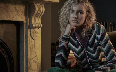 blonde frau im brit chic style vor dem kamin sitzend