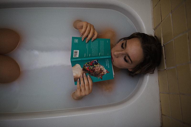 Junge Frau relaxt in Badewanne und liest ein Buch