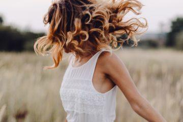 junge frau mit lockigen haaren tanzt über ein feld