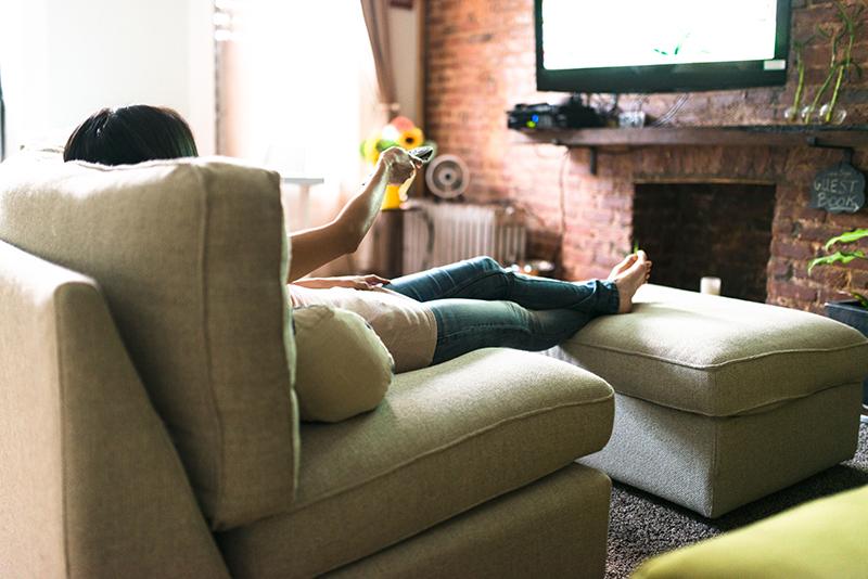 frau relaxt auf dem sofa und schaut fernsehen