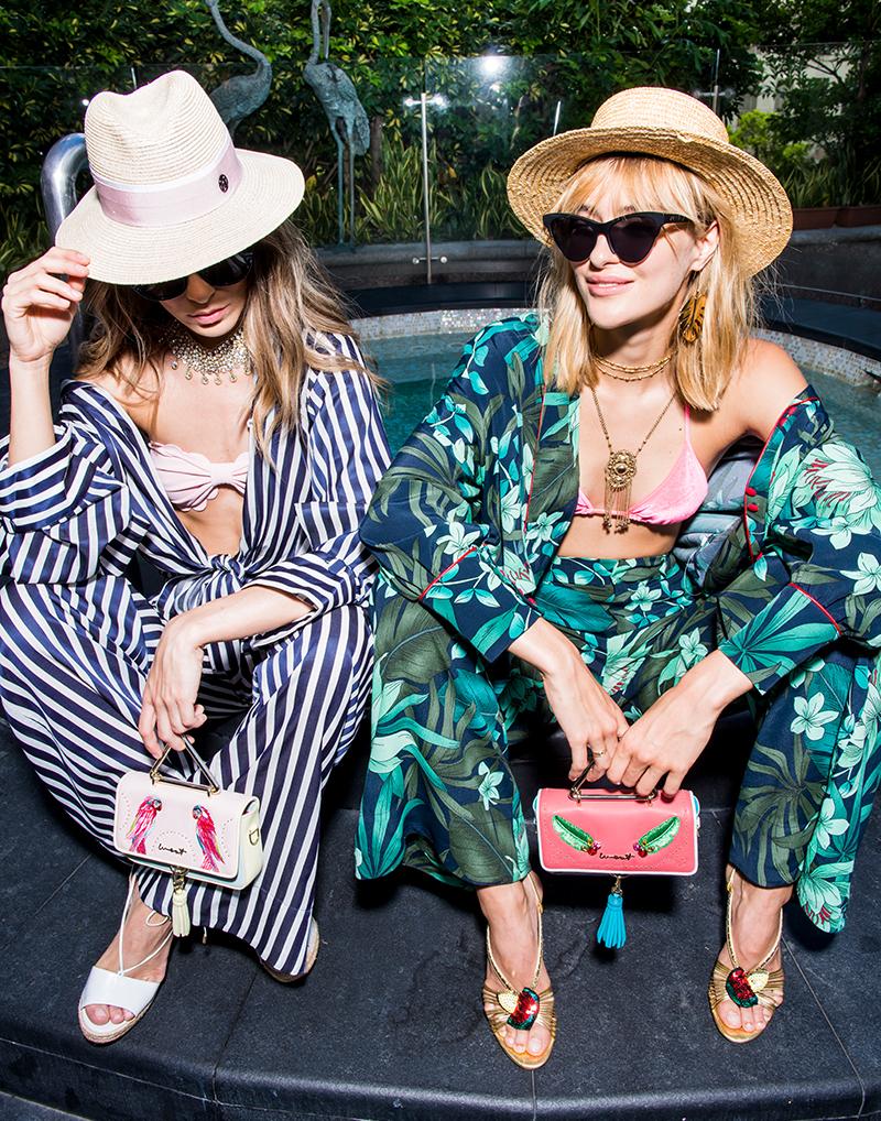zwei junge frauen in der sonne sitzend mit zwei kleinen handtaschen