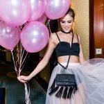 junge frau im tüllrock auf hotel-flur mit luftballons in der hand und einer umgehängten tasche