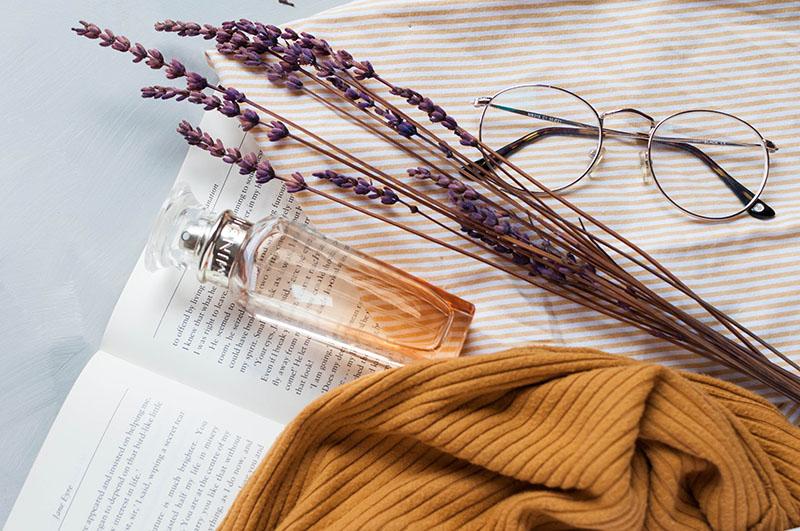 parfum brille buch auf einem tisch liegend