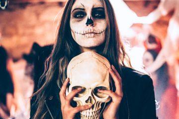 junge frau mit halloween verkleidung und totenkopf in den händen