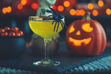 cocktailglas mit einer spinne vor einer halloween deko stehend