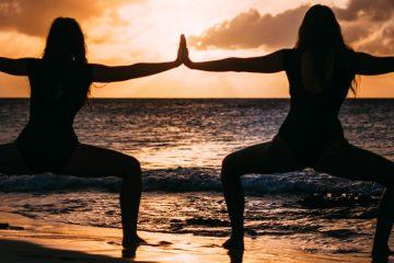 Frauen machen Hormon-Yoga am Strand