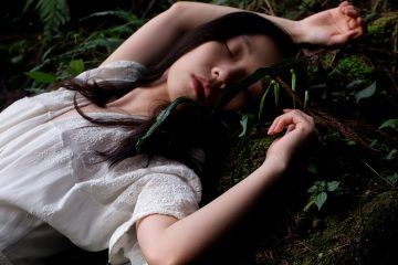 junge frau liegt schlafend im wald