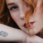junge frau mit roten haaren und kleinem tattoo auf dem arm