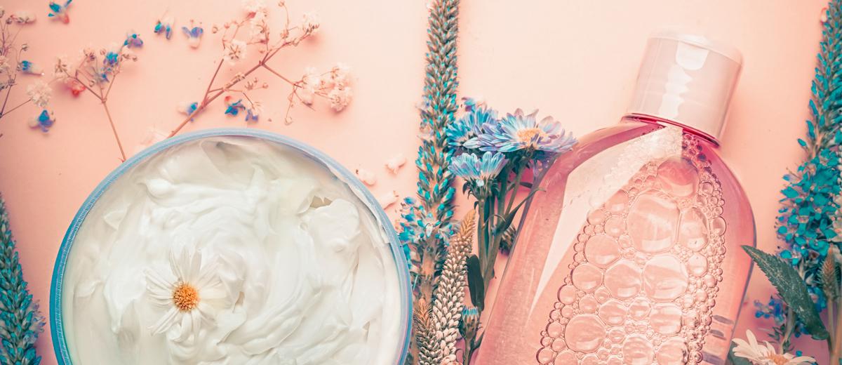 mehrer naturkosmeti produkte dekoriert mit blumen auf eiinem tisch liegend