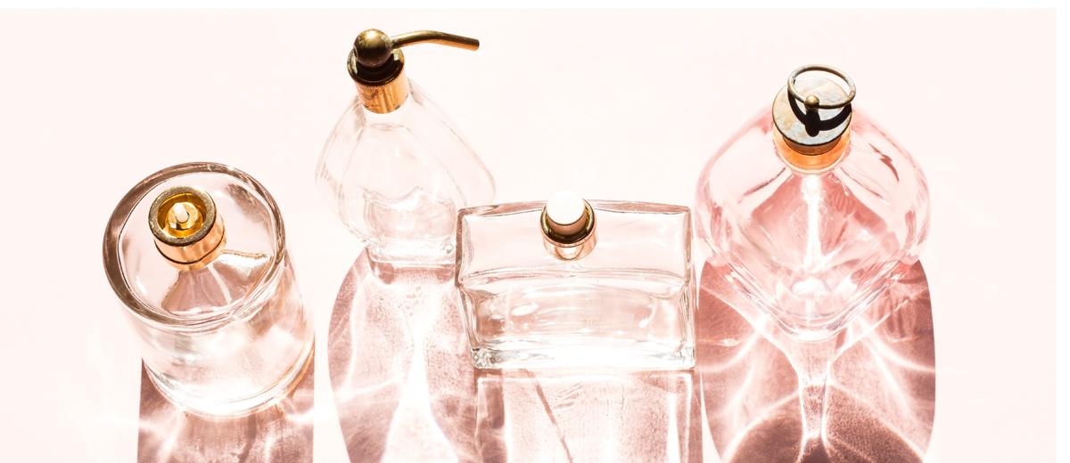 vier parfum flacons auf rosafarbener unterlage