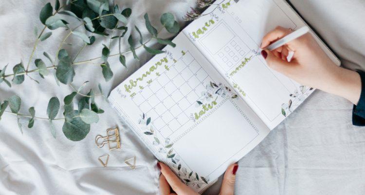 Frauenhand trägt Termine in Kalender ein