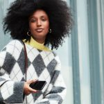 Frau mit Afrolocken trägt Trend-Pullover mit Argyle-Muster