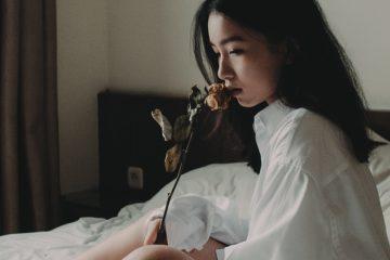 junge frau riecht an einer rose während sie auf dem bett sitzt