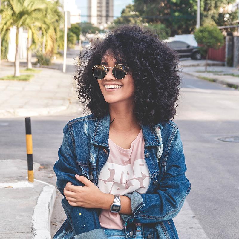 junge frau mit lockigen haaren und einer sonnenbrille lachend auf der straße stehend