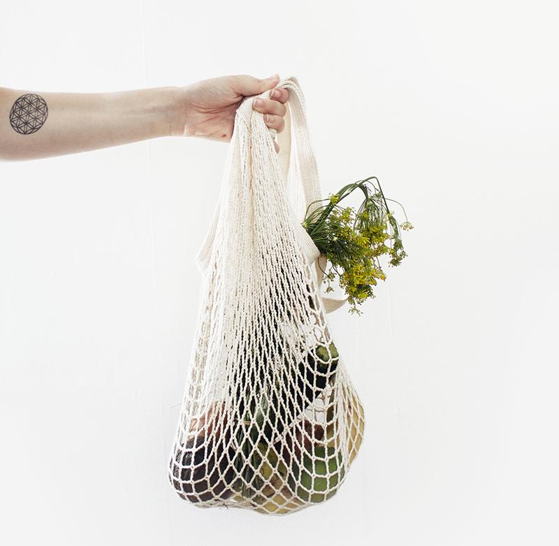 ein hand hält ein netz mit obst und gemüse
