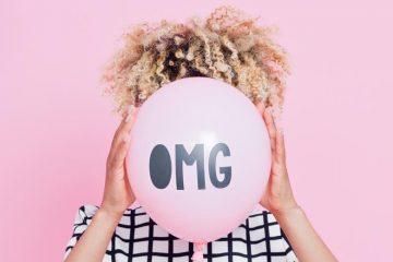 Frau hält sich OMG-Luftballon vors Gesicht