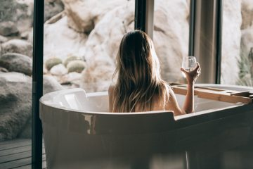 frau mit langen haaren in badewanne sitzemd
