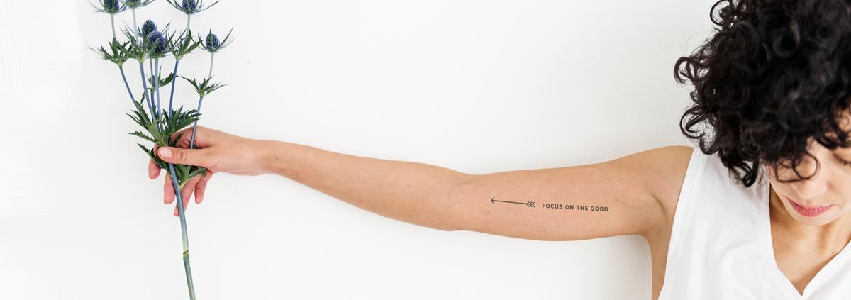 frau mit ausgestrecktem arm hält blumen in der hand