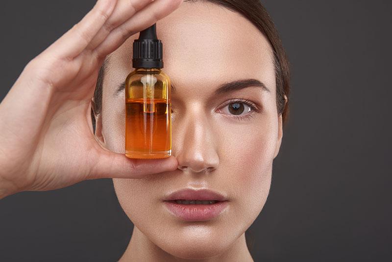 frau hält sich kosmetikfläschchen vor das gesicht