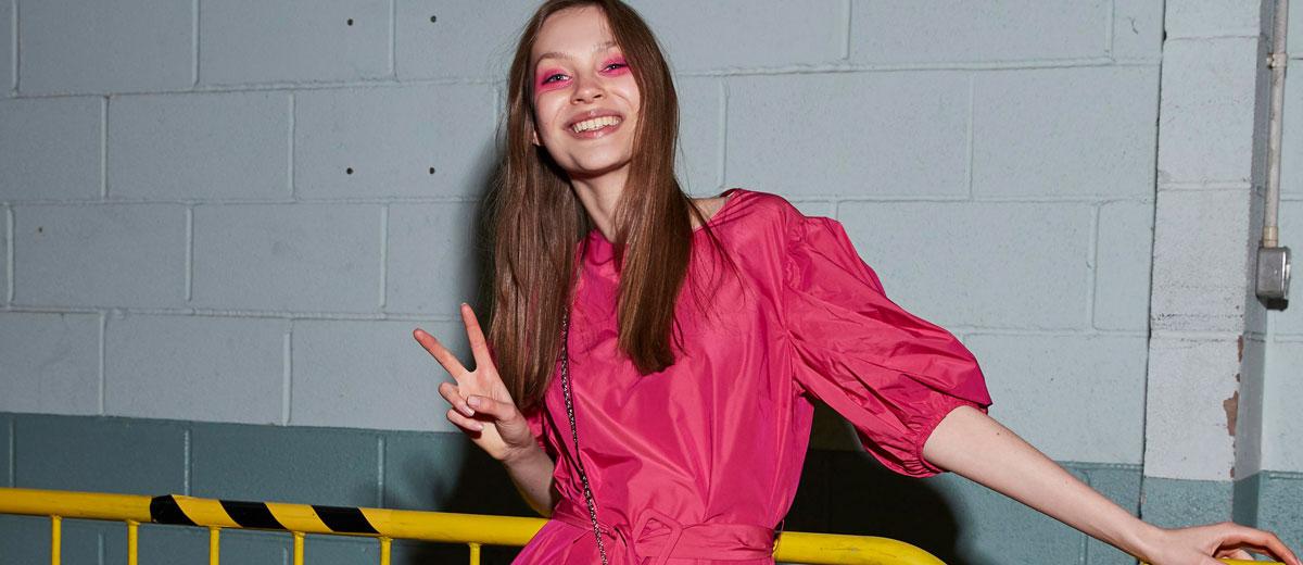 junge frau mit pinkfarbenen lidschatten und kleid