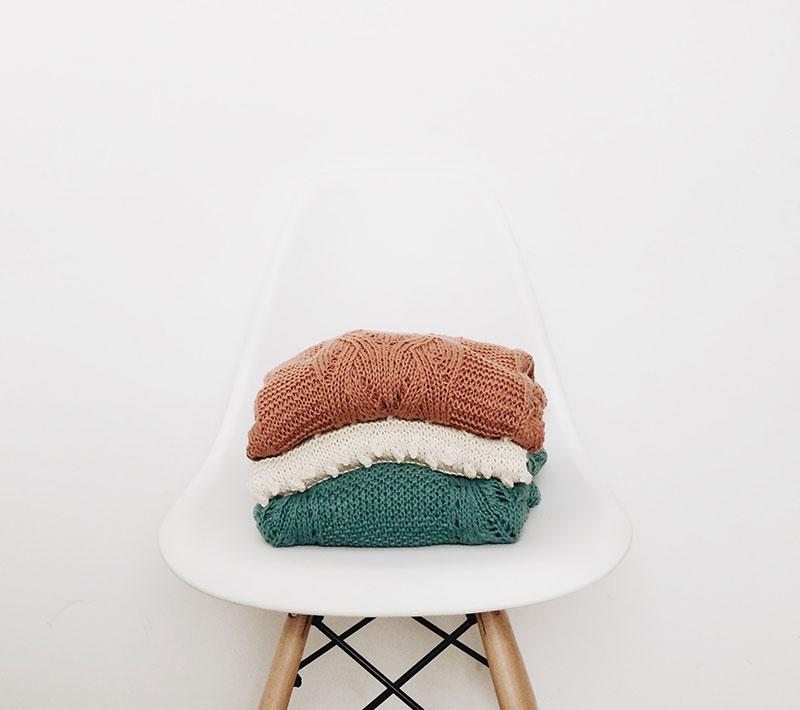 stuhl mit einem stapel pullover