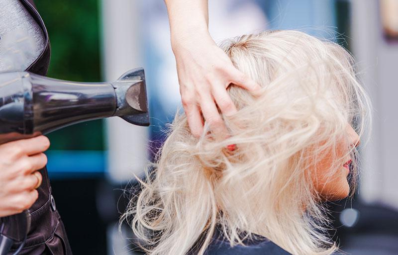 friseur föhnt blonder frau die haare
