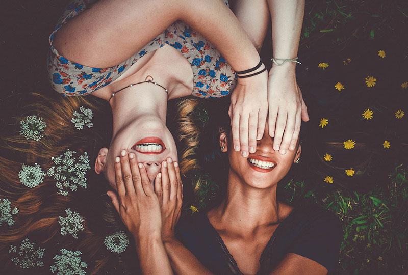 zwei freundinnen liegen im gras und halten sich die augen zu