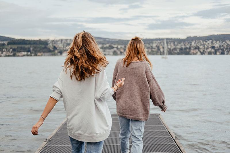 zwei junge frauen auf einem steg