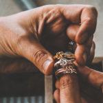 man hält drei ringe in der hand