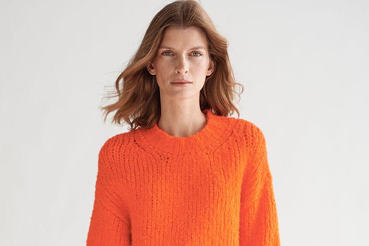 frau im orangenen pullover